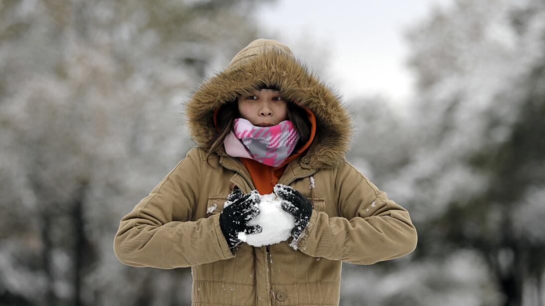 Christine Co makes a snowball while playing in the snow Friday, Dec. 8,...