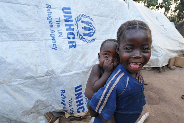 Una niña africana lleba en la espalda a un bebé en un camp...