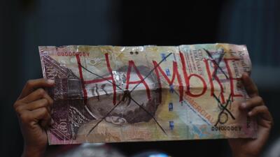 """Billete de 100 bolívares con la paabra """"hambre""""."""