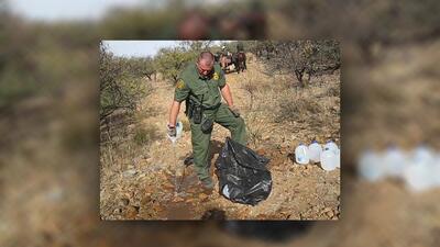 Un agente de la Patrulla Fronteriza tira el agua de uno de los galones q...