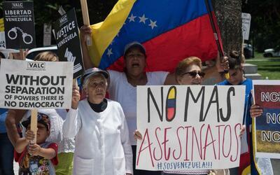 Un grupo de venezolanos protesta contra su gobierno en Cancún, en...