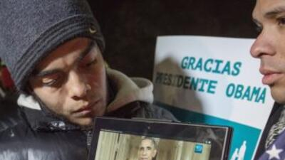 Dos inmigrantes indocumentados en las afueras de la Casa Blanca escuchan...
