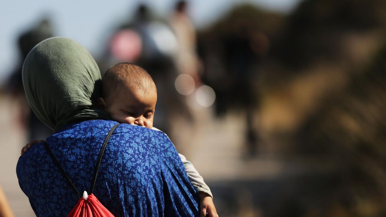 Una mujer siria con un bebé en brazos busca refugio en Grecia huyendo de...