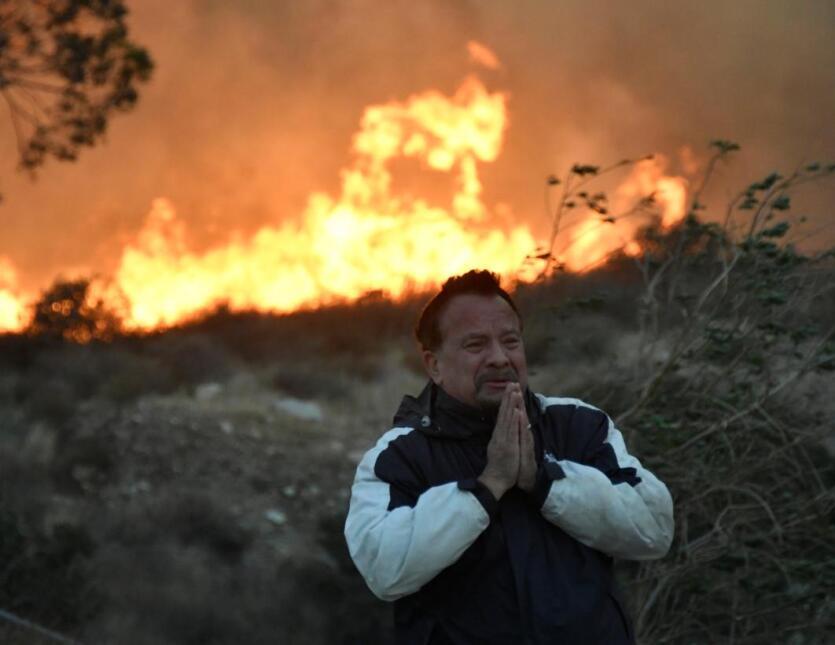 Un hombre reza junto al fuego Creek mientras este se propagaba por el va...