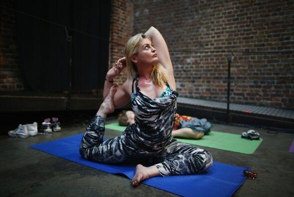 Una mujer hace yoga durante una Morning Glory 'Rave a su manera en el dí...