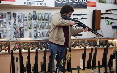 Un cliente evalúa un rifle en una tienda de New Hampshire el 5 de...