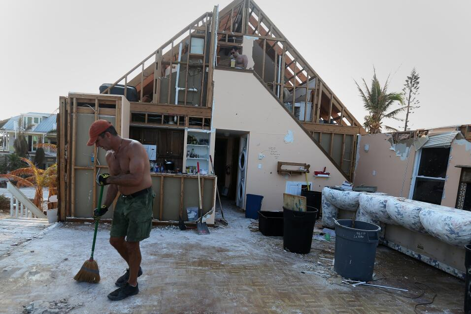 Mike Phillips works on cleaning up what was once his living room of his...