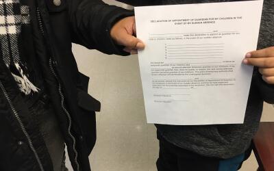 María (nombre ficticio) y su hijo sostienen una carta de custodia temporal.