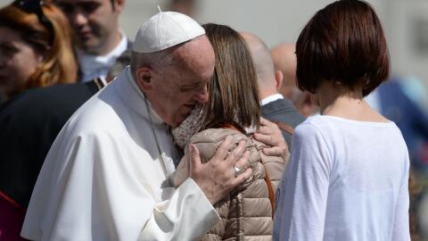 Francisco abraza a una mujer durante una audiencia general en San Pedro,...