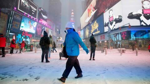 Transeúntes se abren paso en la nieve que cubre a Times Square, e...