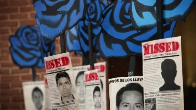 Activistas cuelgan carteles de los estudiantes de Ayotzinapa durante una...