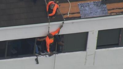 Rescatan un hombre que quedó colgando de un arnés en el techo de un edificio