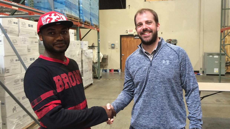 Un refugiado da la mano a un empleador, quien usó los servicios de la fi...