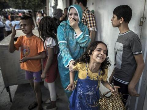 Una mujer y una menor lloran tras un ataque aéreo israelí...