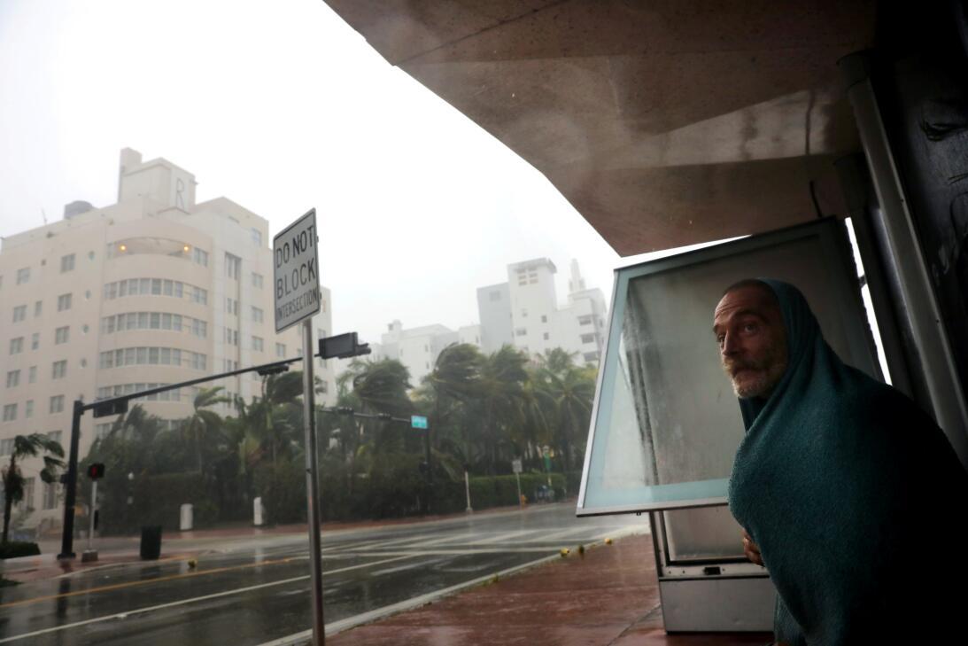 Un hombre sin hogar se refugia en una parada de autobús en Miami Beach c...