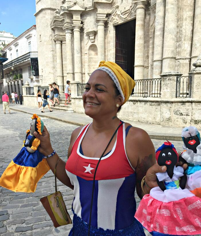 A Cuban woman sells homemade souvenir dolls in the Cathedral Plaza in Ol...