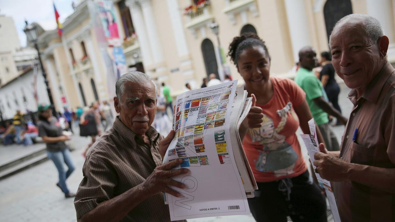 Un hombre sostiene un papel que muesta cómo serán las papeletas de votac...