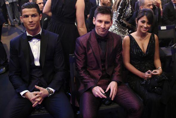 Ya sentados en sus lugares, Cristiano y Messi, acompañado por su novia A...