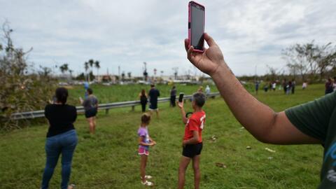 Residentes buscan señal para sus teléfonos móviles...