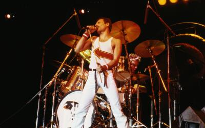 Freddie Mercury (1946-1991), singer with Queen, standing in front of a d...