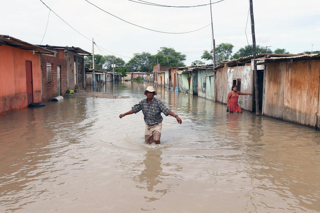 Un poblador trata de cruzar una calle inundada por las lluvias torrencia...