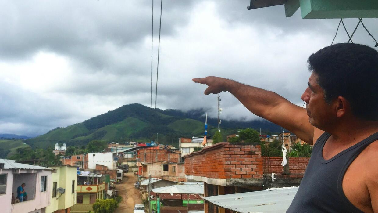 Adolfo López points to the could-covered hilltop where the FARC's...