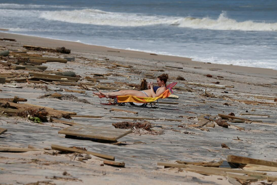 A woman suntans amongst debris on the beach after Hurricane Irma passed...
