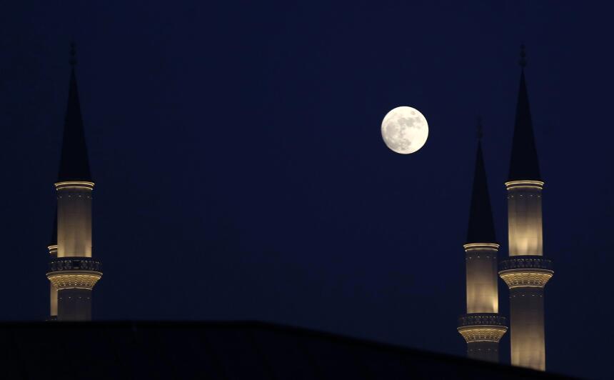 La luna se observa entre los miranetes de una mezquita en Ankara (Turquía).