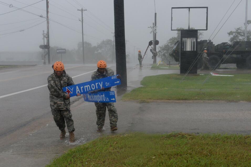 Personal militar recoge escombros bajo la lluvia en Victoria, Texas.