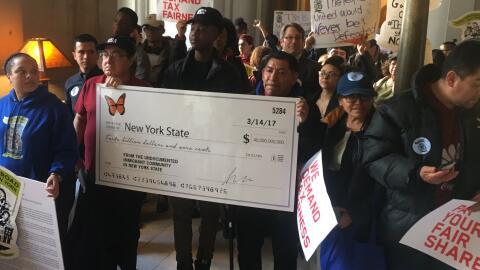 Miembros de la comunidad inmigrante cargan un cheque simbólico que le en...