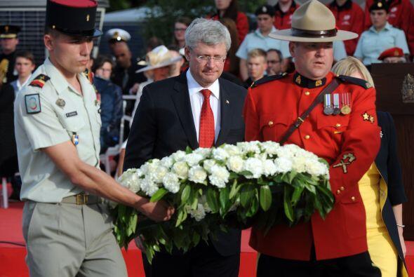 El primer ministro de Canadá, Stephen Harper, sostiene una corona de flo...