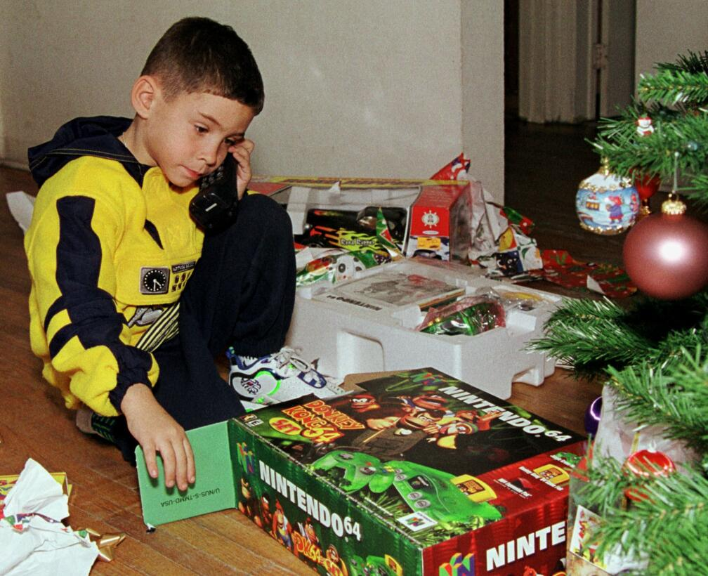 Elian Gonzalez, 6, looks at one of his Christmas presents at his relativ...