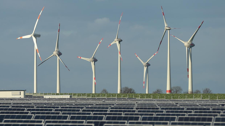 Wind turbines + solar Wind turbines stand behind a solar power park near...