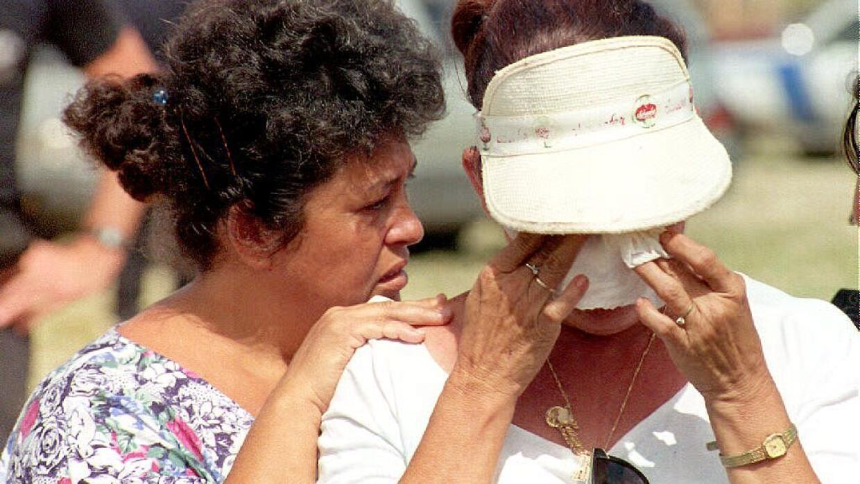 Gladys Miranda conforta a su hermana Carmen durante un servicio para hon...