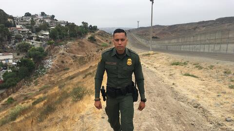 Eduardo Olmos, agente fronterizo, camina en la franja que separa a Tijua...