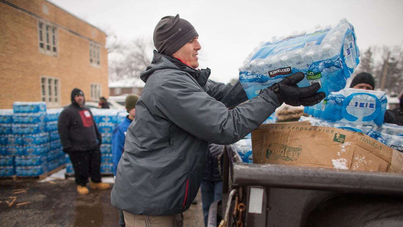 Voluntarios cargan cajas de agua a unos autos esperando en Salem Luthera...