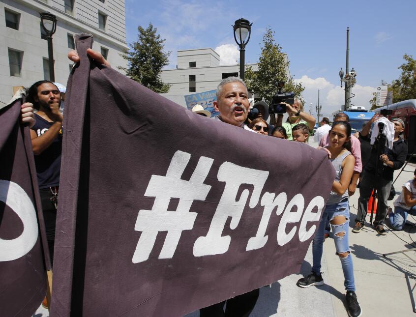 """Rómulo Avélica sostiene un fragmento de una manta que dice """"Libre""""."""