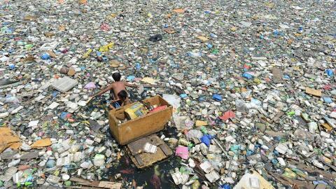 Padre e hijo se ganan la vida recogiendo plástico en un rí...