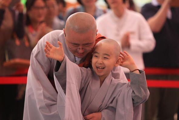 Este pequeño monje se pone sonriente junto a su  líder.