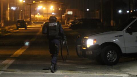 Un policía federal camina entre calles oscuras de México (...