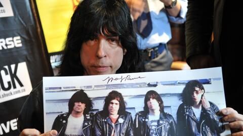 Marky Ramone firmando autógrafos sobre un afiche de la banda en s...