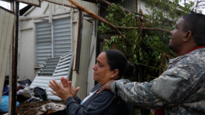 Una familia contempla su casa destrozada en Guayama, Puerto Rico.