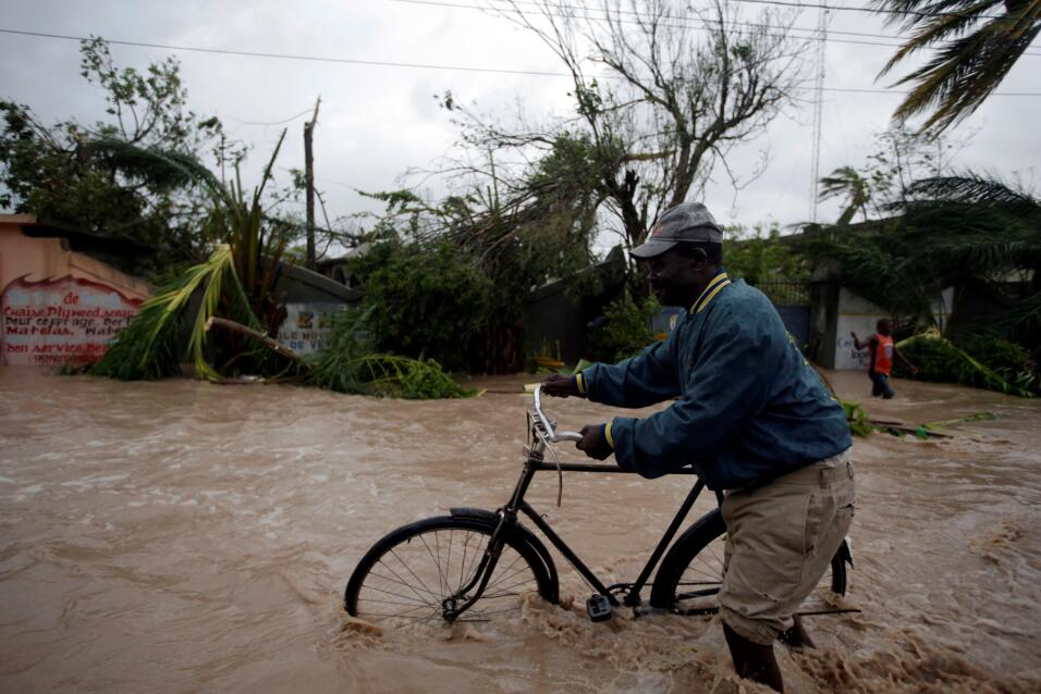 Man wheels a bicycle through flood waters in Les Cayes, southwest Haiti