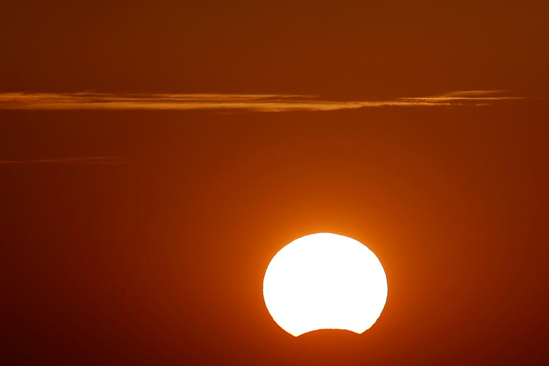 """A partial eclipse of the sun, as it sets, is seen from the """"Puerto..."""