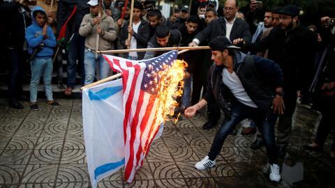Palestinos queman una bandera israelí y una estadounidense en una...
