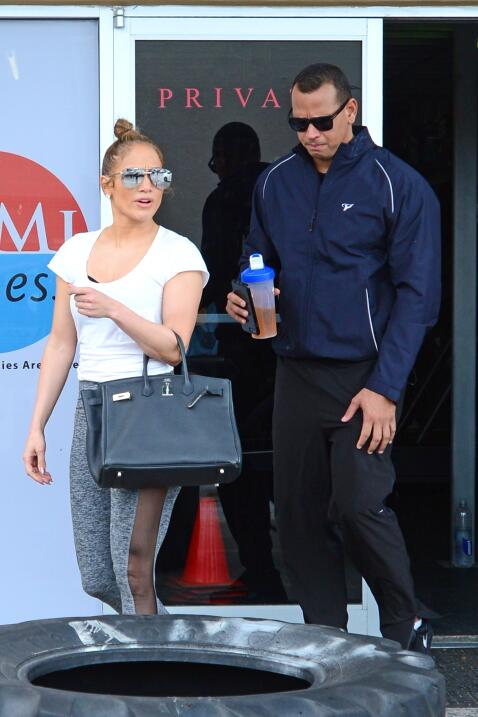 Jennifer Lopez and Alex Rodriguez greet their trainer as they stop by a...