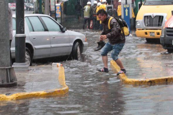 Este joven intenta brincar de una acera a otra para no pisar la inundación.