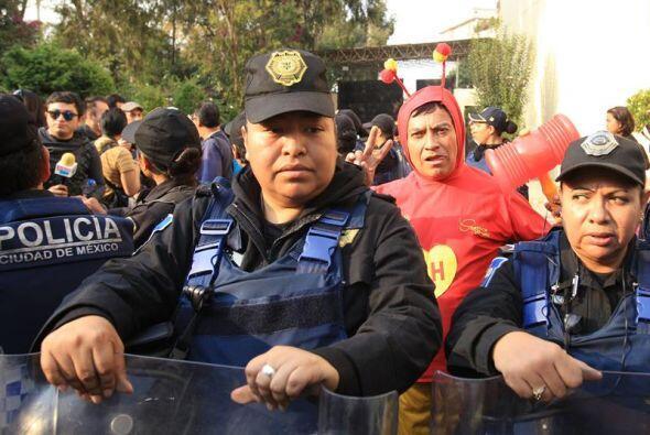 Un fanático de El Chapulín Colorado, detrás de un grupo de policías
