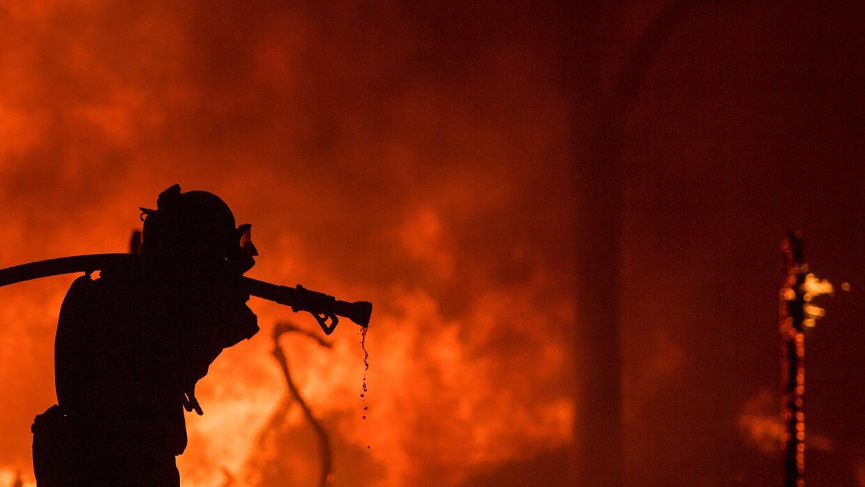 Un bombero saca una manguera frente a una casa en llamas en la regi&oacu...
