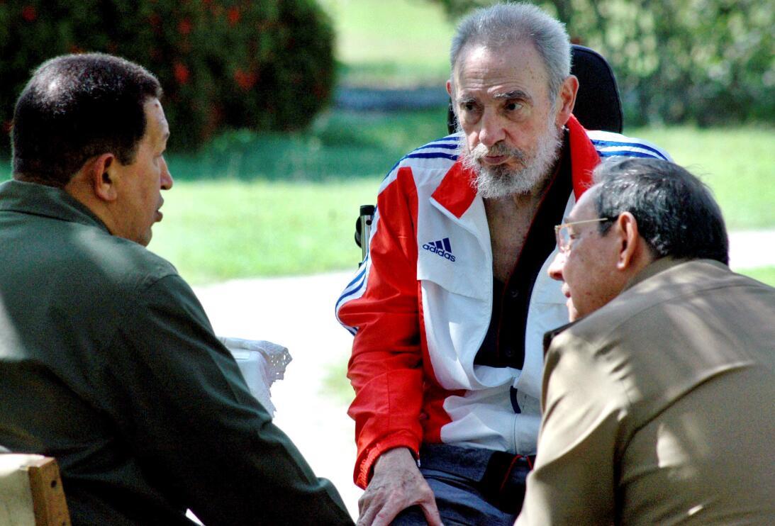 Fidel Castro (centro) junto con su hermano Raúl (dercha), que asumió el...